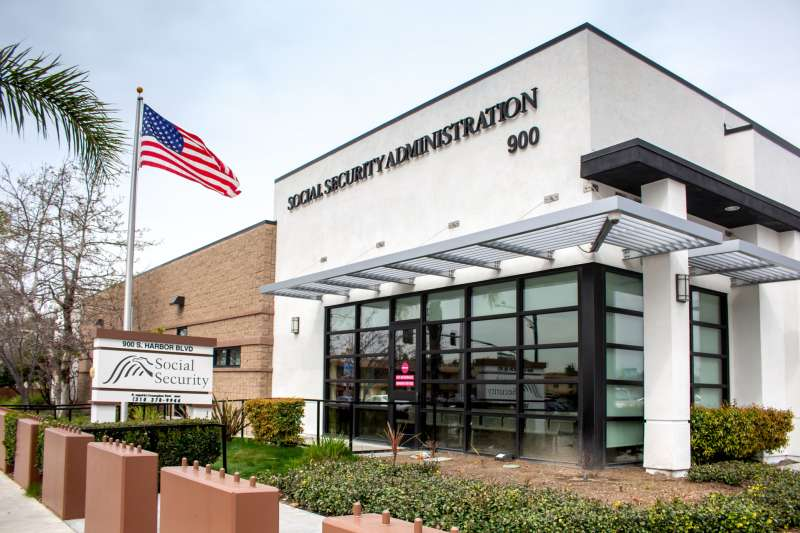 A local Social Security Administration building with an American flag at the entrance