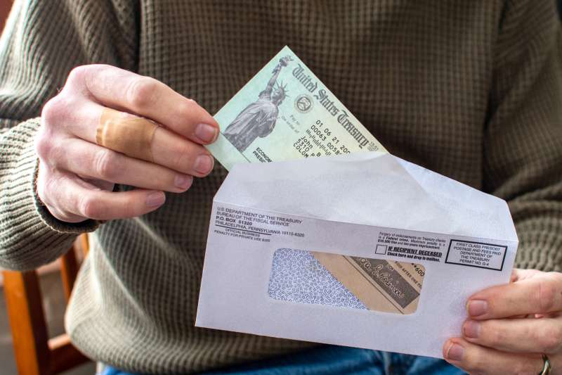 Closeup of a person taking a stimulus check out from an envelope