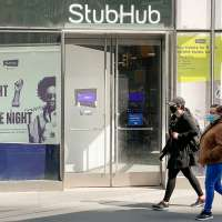 People wear face masks as they walk by a StubHub location in New York City