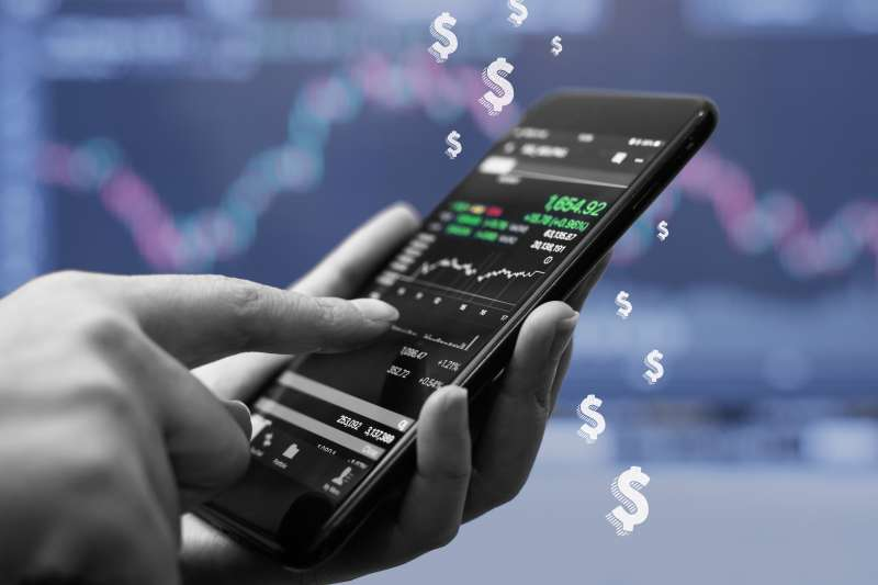 A close up of a hand holding a phone purchasing stocks on a trading app with some dollar signs in the background.