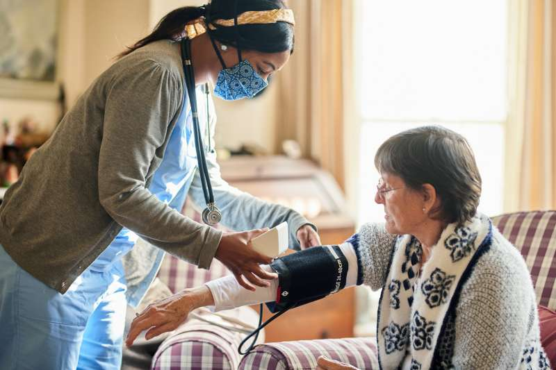 Young nurse wearing a protective face mask taking a senior patient's blood pressure