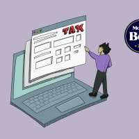 Person Standing On Top Of An Oversized Laptop With The Word Tax On The Screen