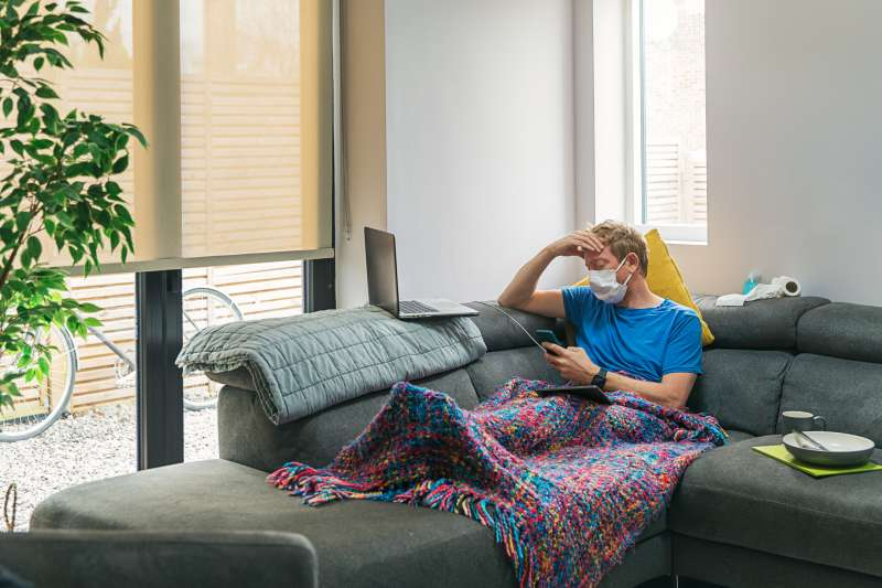 Man sick with Covid-19 isolated and wearing a face mask in his living room