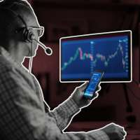Man Holding Smart Phone While Staring At A Computer Screen Displaying Stock Market Graphics
