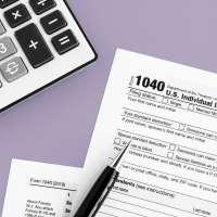 Close up of a 1040 Tax Return form, a pen and a calculator