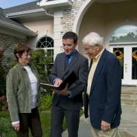 Real estate agent showing a new home to a senior couple