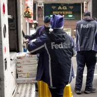 A Fedex employee wearing a Santa Claus hat takes packages off a truck in New York City