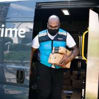 Amazon driver carrying packages out of a Prime truck