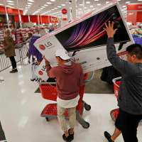 Two Men In A Store During Black Friday Placing TV Box Into A Shopping Cart
