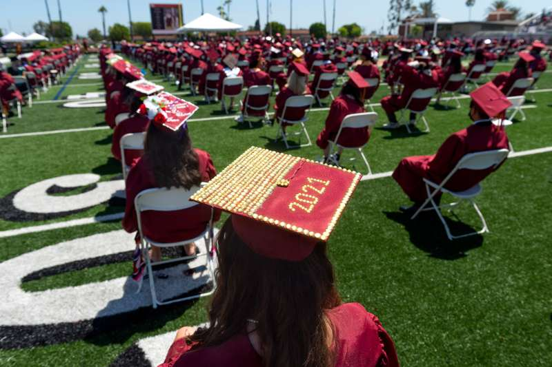 A graduate wears a decorated 2021 cap during commencement for El Modena High School