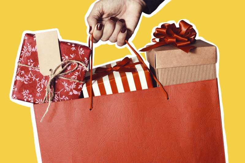 Closeup of a hand holding a bag with multiple gifts inside wrapped in holiday themed paper