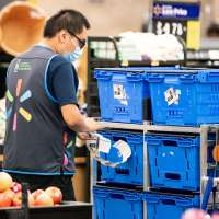 A Walmart employee restocks fruit and vegetables at a Walmart Supercenter