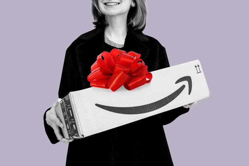 Closeup of a woman holding an Amazon delivery box with a big red gift bow on top.